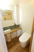 トイレ 横幅を少し広く取っています。オーク材のカウンターや、スペースにあわせた造作家具、また間接照明も設置し落ち着いた空間となりました。